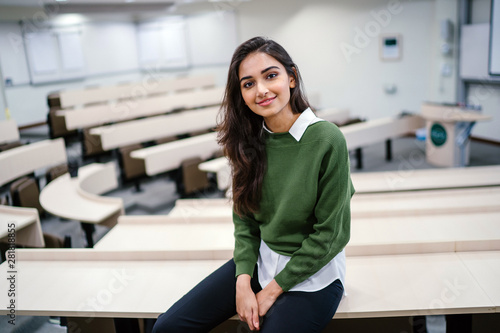 Portrait of a beautiful, young and attractive Indian Asian business woman smiling as she sits in a seminar room during the day Wallpaper Mural