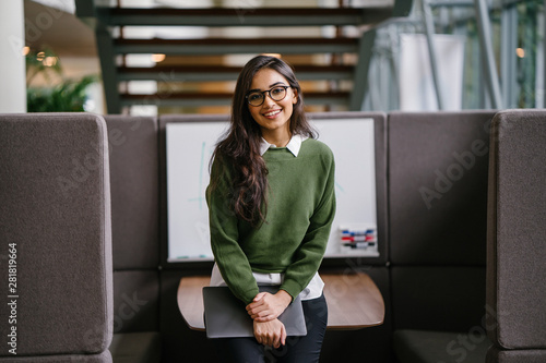 Portrait of a young, beautiful, intelligent and attractive Indian Asian MBA student smiling as she leans in a discussion booth in her campus Wallpaper Mural
