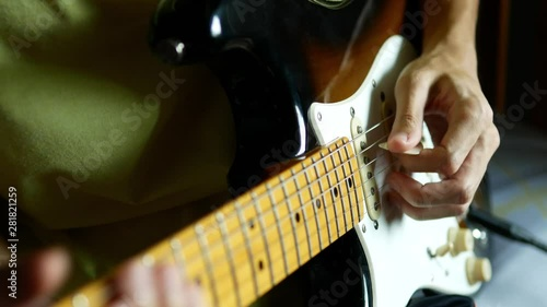 Fotografia, Obraz  Lefthander playing electric guitar by holding pick by left hand.