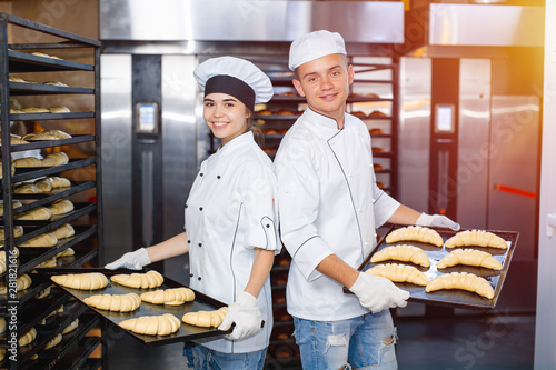 Fotografie, Obraz baker boy and girl with baking sheets with raw dough on the background of an industrial oven in a bakery