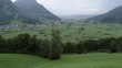 Perspective view of the Linth rivers valley surrounded by alpine montains near Glarus Nord in Switzerland. Scenic shot taken from hill-side on a cloudy day with the valley and mountains in foreground.