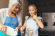 canvas print picture - Grandmother and kid having fun making cake in kitchen