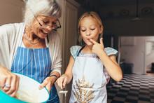 Grandmother And Kid Having Fun Making Cake In Kitchen