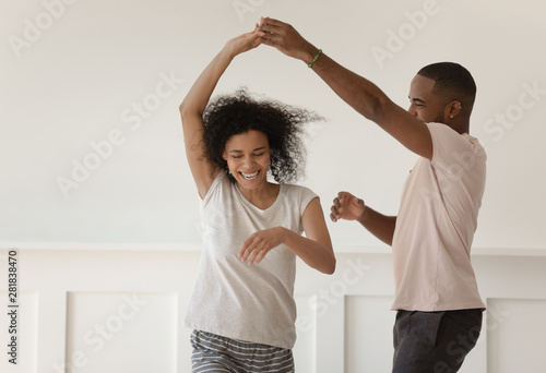 Happy young african couple holding hands dancing laughing at home - 281838470