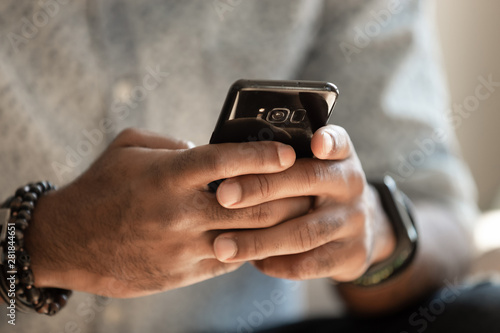 Fotografía  African man holding cellphone using applications, close up view