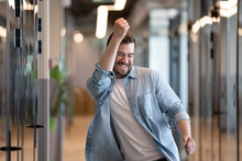 Ecstatic Male Winner Dancing In Office Hallway Laughing Celebrating Success