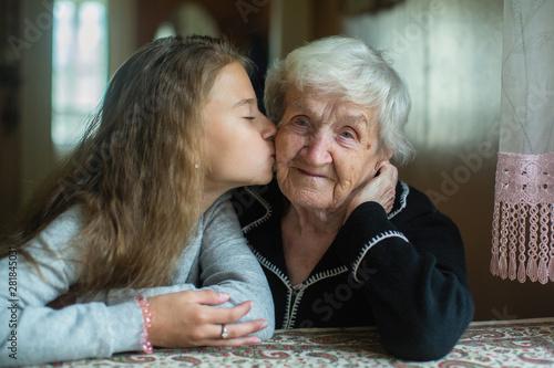 Obraz An elderly grandmother with her little granddaughter. - fototapety do salonu