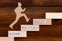 Good - Better - Best,  Paper Man Climbing The Steps To Success In A Conceptual Image Over Wooden Background