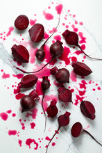 Washed And Cut Baby Beetroots On A Marble Tile Surface, With Juice Splashes.