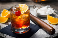 Old Fashioned Cocktail On Ice With Cherry And Orange Garnish, Sugar Cubes, And Muddler On Tray