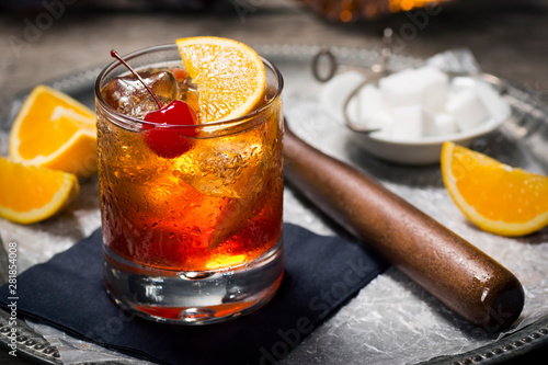 Obraz Old Fashioned Cocktail On Ice with Cherry and Orange Garnish, Sugar Cubes, and Muddler on Tray - fototapety do salonu