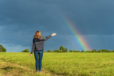 Fototapeta Tęcza - A woman with raised hands is standing in a field against the sky decorated with a rainbow after the rain.