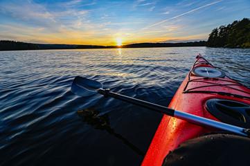 crveni plastični kajak na mirnoj vodi u zalasku sunca