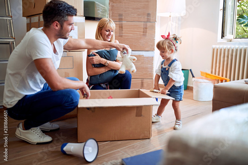 Photo  Young family after buying new house unpacking boxes.