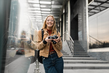 Portrait Of Professional Photographer In Stylish Eyeglasses Holding Digital Camera Outdoors. Smiling Hipster Woman With Beautiful Emotional Face Walking Around Urban Street. Successful Hobby