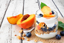 Healthy Peach And Blueberry Parfait In A Mason Jar, Close Up On A White Wood Background