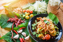 Papaya Salad Served On Wooden Dining Table / Green Papaya Salad Spicy Thai Food On Plate With Sticky Rice Herbs And Spices Ingredients With Chilli Tomato Peanut Garlic Som Tum Thai Menu Asian Food
