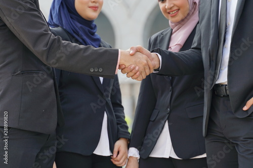 Fotografía  Muslim Asian business people shaking hands with new partner, business co-working teamwork concept