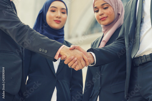 Fotomural  Muslim Asian business people shaking hands with new partner, business co-working teamwork concept