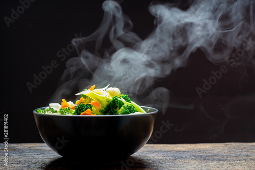 Cuadros en Lienzo  The steam from the vegetables carrot broccoli Cauliflower in a black bowl , a steaming