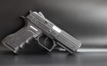 Black 9 Mm Pistol On A Gray Background