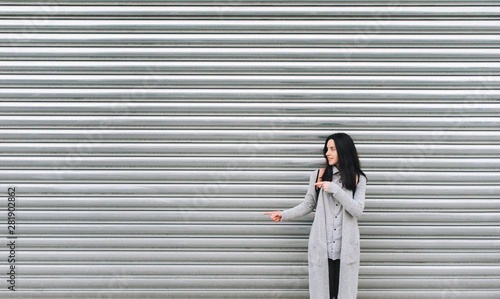 Cuadros en Lienzo  A young European girl in a gray cardigan stands against a metal textured wall and smiles, pointing her fingers to the left side of the background