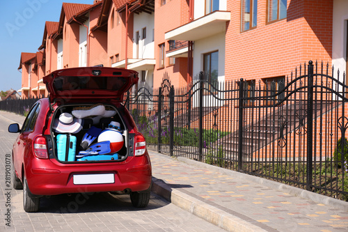 fototapeta na szkło Family car with open trunk full of luggage in city. Space for text