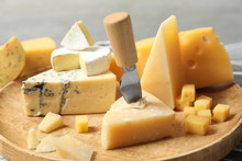 Different Types Of Delicious Cheese In Wooden Plate, Closeup