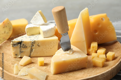 Fototapeta Different types of delicious cheese in wooden plate, closeup obraz