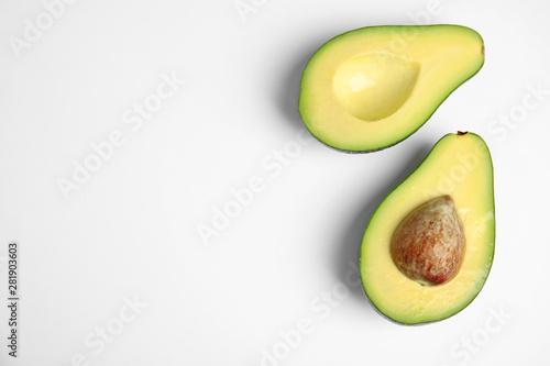 Cut fresh ripe avocado on white background, top view Fototapeta