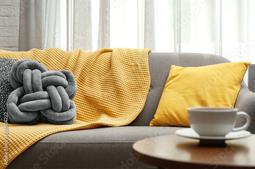 Obraz Soft pillows and yellow plaid on sofa in living room - fototapety do salonu