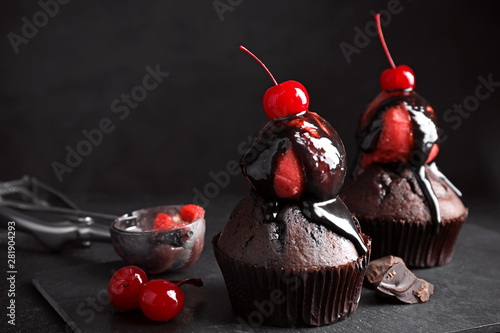 Photo  Delicious chocolate muffins with sweet syrup, ice cream and cherries on table