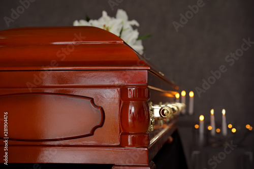 Fotografia Wooden casket with white lilies in funeral home, closeup