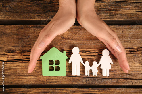 Foto Woman holding hands near figures of house and family on wooden background, top v