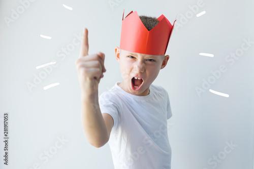 Fototapeta  child dictator red paper crown establishes rules