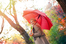 Woman With Red Umbrella Walking On Autumn Park
