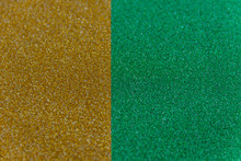 Golden And Green Sparkling Background From Small Sequins, Closeup. Brilliant Shiny Backdrop From Textile. Shimmer Paper