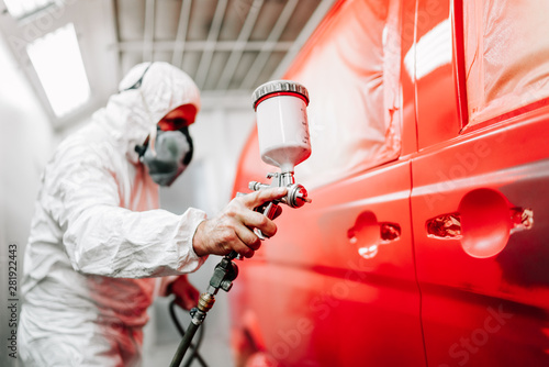 Cuadros en Lienzo Close-up of worker using spray gun and airbrush and painting a red car