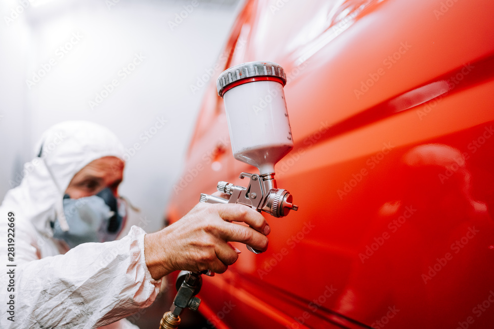 Fototapety, obrazy: mechanic worker painting a car in a special painting box, wearing a full body costume and protection gear