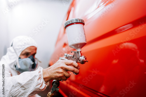 Photo mechanic worker painting a car in a special painting box, wearing a full body co
