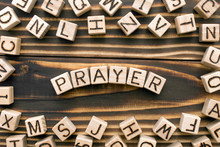 Prayer - Word From Wooden Blocks With Letters, Speaking To God Concept, Random Letters Around, Top View On Wooden Background