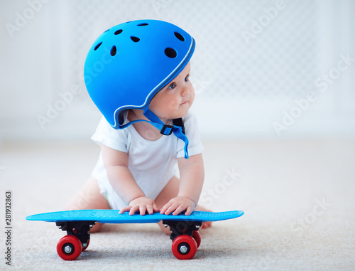 cute infant baby girl in protective helmet outfit ready to ride skateboard, extr Fototapeta