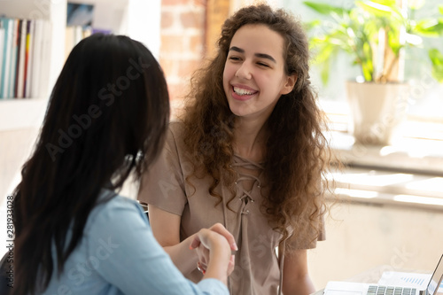 Photo Young women sitting at desk smiling shake hands