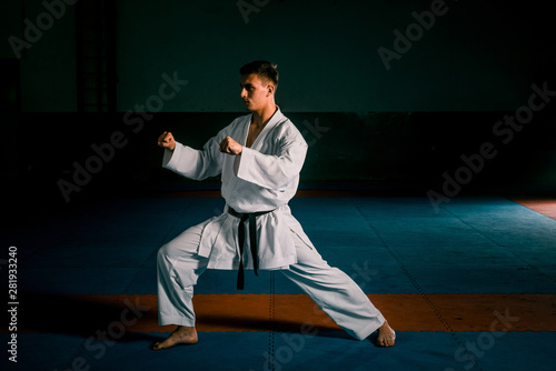Photo  The karate guy in white kimono and black belt training karate
