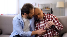 Sad Son Calming Disabled Senior Father, Health Problems, Suffering Strong Pain