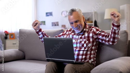 Photo Cheerful elderly man getting answer on dating site, receiving good news, luck