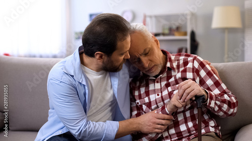 Middle-aged son comforting retiree terminally ill father, suffering pain, care Tableau sur Toile