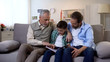 Happy grandpa, adult son and grandson viewing photos in album together, memories