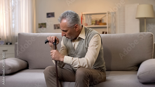 Retired man with cane sitting on sofa, loneliness and depression, problems