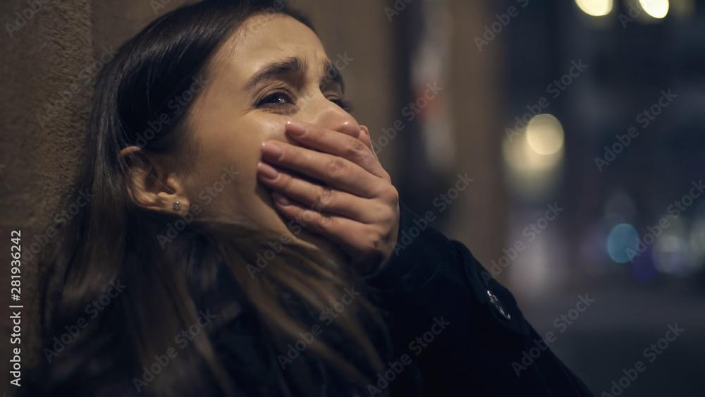 Fototapeta Shocked robber victim crying at night street, panic attack, psychological trauma